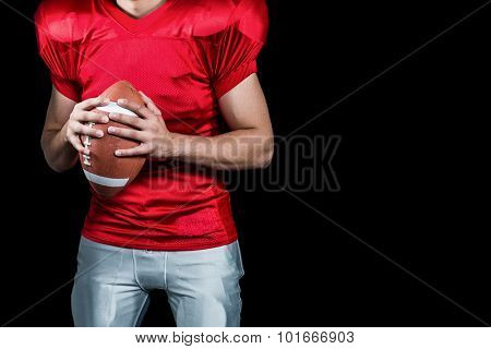 Mid section of American football player holding ball against black background
