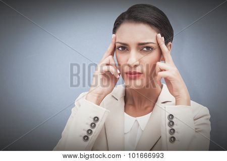Young businesswoman putting her fingers on her temples against blue background