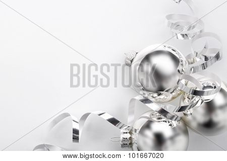 Silver Christmas balls and ribbon on white background