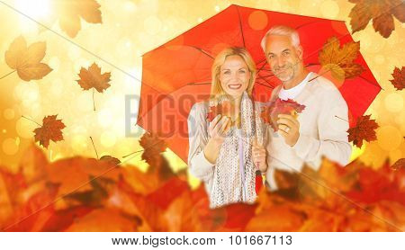 Portrait of happy couple under red umbrella against yellow abstract light spot design