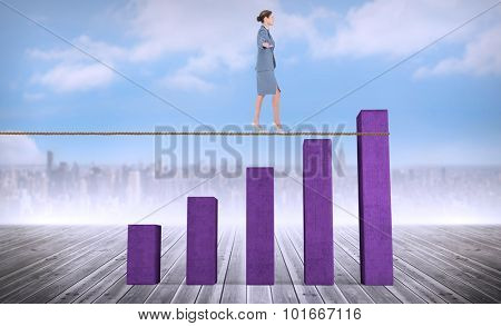Businesswoman walking tightrope against bar chart depicting growth