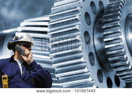 industry worker, mechanic with large gears and cogwheels machinery, blue toning