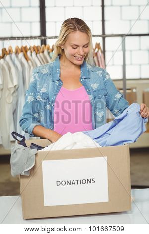 Woman separating clothes from donation box while standing in office