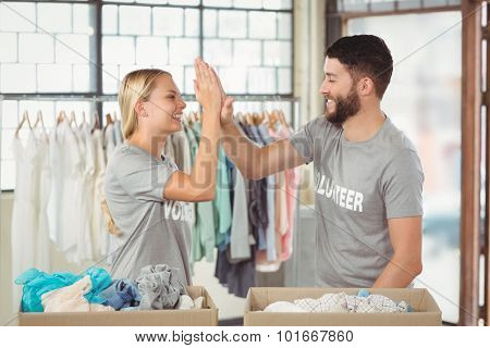 Happy volunteer doing high five while working at office