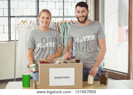Portrait of smiling volunteers separating donations stuffs in office