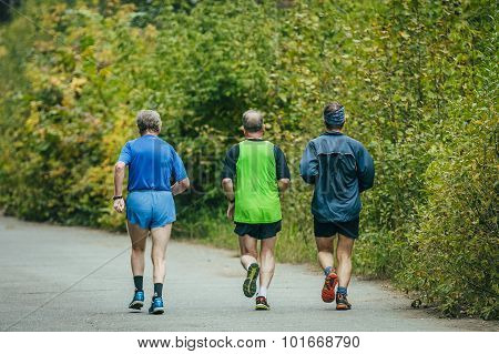 group of older men running down the road in Park