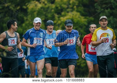 group of middle-aged joggers running in Park