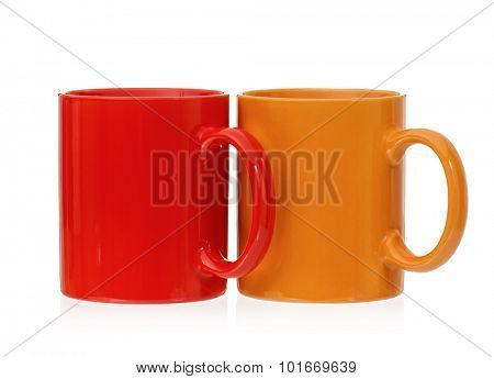 Two mugs - orange and red, isolated on white background