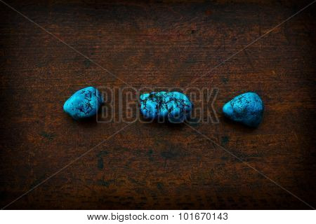Turquoise stone placed on rustic wooden table.
