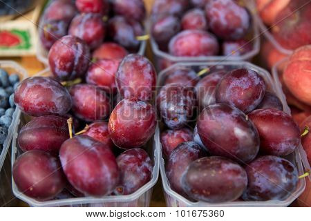 sale, harvest, food, fruits and agriculture concept - close up of satsuma plums in plastic boxes at street market