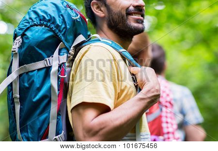 adventure, travel, tourism, hike and people concept - close up of friends walking with backpacks in woods