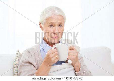 health care, flu, cold, age and people concept - sick senior woman with paper napkin drinking hot tea at home