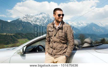 travel, tourism, road trip, transport and people concept - happy man near cabriolet car over mountains background