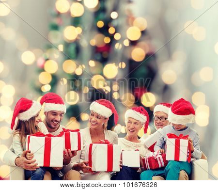 family, happiness, generation, holidays and people concept - happy family in santa helper hats with gift boxes sitting on couch over christmas tree lights background