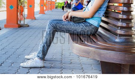 Girl Sitting On Bench And Looking At The Front.