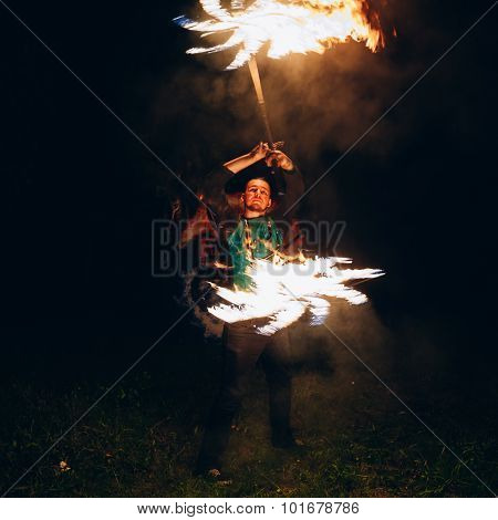 Fire Show at night. Young man stands in front of an audience wit
