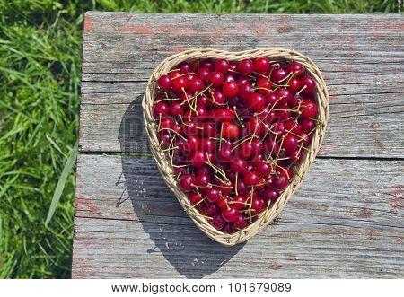 Ripe Cherries In Wicker Basket On Wooden Table