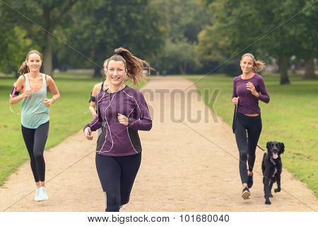 Four Athletic Girls Jog At The Park