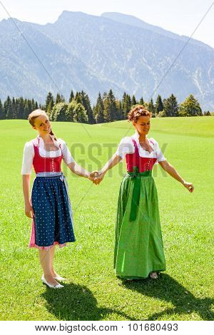 Mother And Daughter Walking Both Go Hand In Hand In A Dirndl.