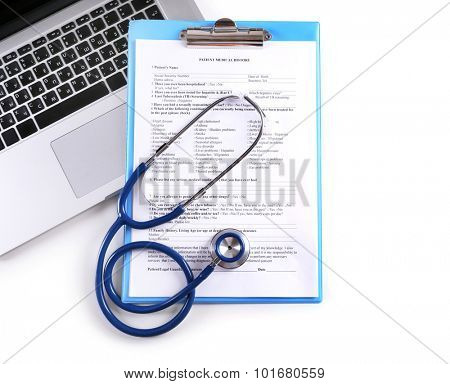 Stethoscope with medical history and laptop isolated on white
