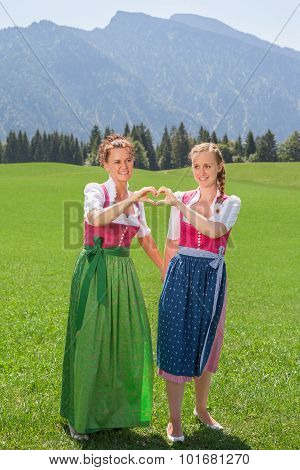 Two Women In Dirndl Forming A Heart With Her Hands