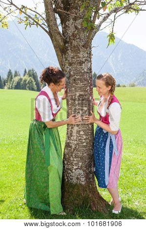 Two Bavarian Women Cling To A Tree And Smile At Each Other