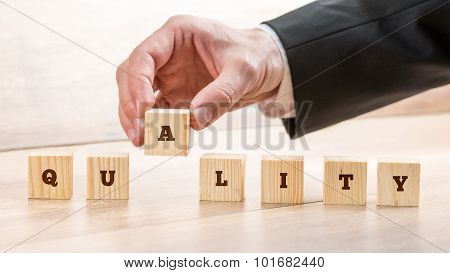 Businessman Assembling The Word Quality With Seven Wooden Cubes