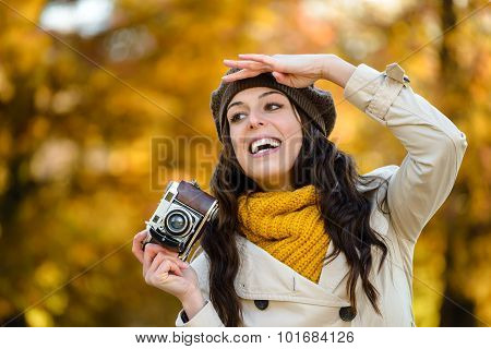 Happy Woman With Camera Looking For Autumn Photo