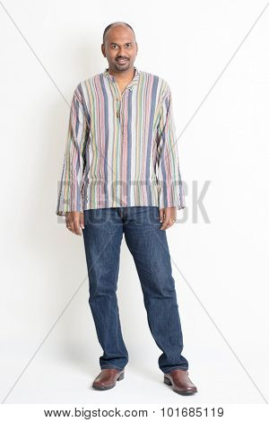 Full body mature casual Indian man standing on plain background with shadow.