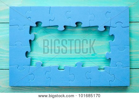 Puzzle Frame On Blue Wooden Surface