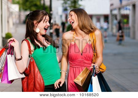 women downtown shopping with bags