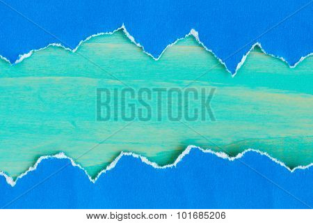 Torn  Paper With A Blue Wooden Background