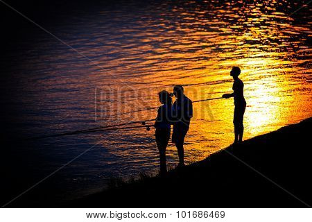 Abstract fisher figures on sea shore against sunset background
