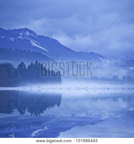 Landscape with morning fog on mountain lake