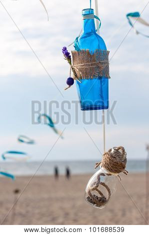 Decorative vintage blue bottle and wicker jar with seashell on sea background