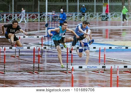 young athletes run 110 meter hurdles  in the rain