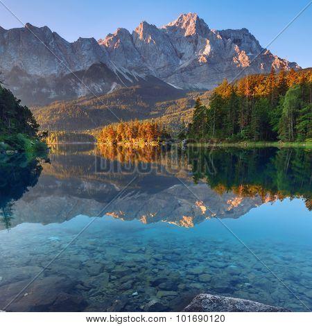 Fantastic sundown on mountain lake Eibsee, located in the Bavaria, Germany. Dramatic unusual scene. Alps, Europe.