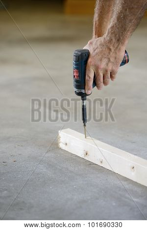 Closeup of Hands of Worker Using Drill