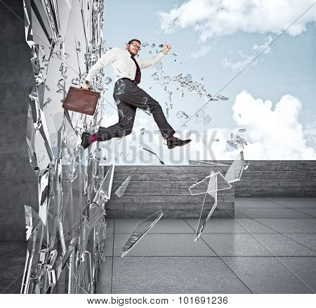 smiling businessman broke glass with jump