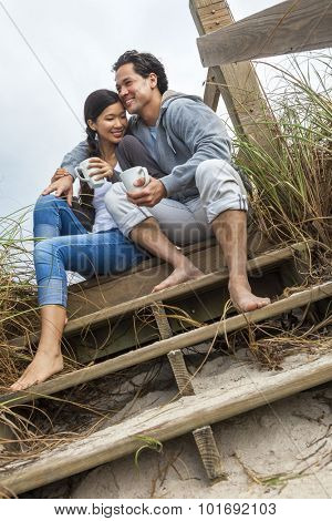 Young Asian Chinese man & woman, boy & girl, couple sitting on wooden steps overlooking a beach drinking mugs of tea or coffee