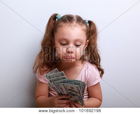 Unhappy Confused Grimacing Kid Girl Looking On Dollars In Hands And Thinking How Small She Have Earn