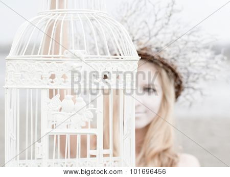 Fairy woman holding birdcage outdoor