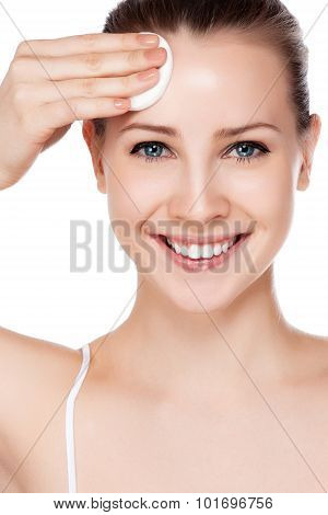 Beautiful woman cleaning her pretty face with cotton swab - over white background