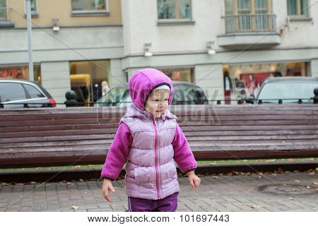 Toddler girl with warm hoodie in city centre at display windows and cars background