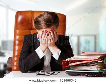Portrait Of Mature Disappointed Businesswoman Sitting At Desk In Office