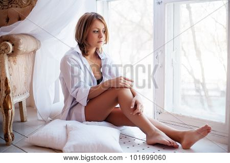Portrait Of Charming Girl  Sitting On Windowsill And Looking Through Window