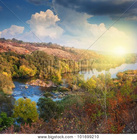 Valley of River in Autumn, beautiful sunny day, colorful trees and clouds, panoramic view