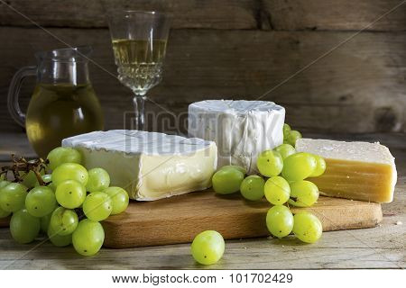 Various Cheese With Grapes And Wine On Dark Rustic Wood