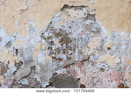 Old vintage painted plastered wall abstract background with many layers of worn paint in various colors and broken plaster texture