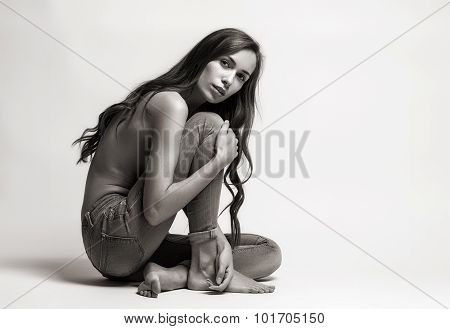 Fashion Model Sitting On A Floor In A Jeans Barefoot On A White Background